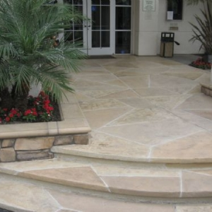 Concrete commercial front entry covered in multicolored random stone Tuscan